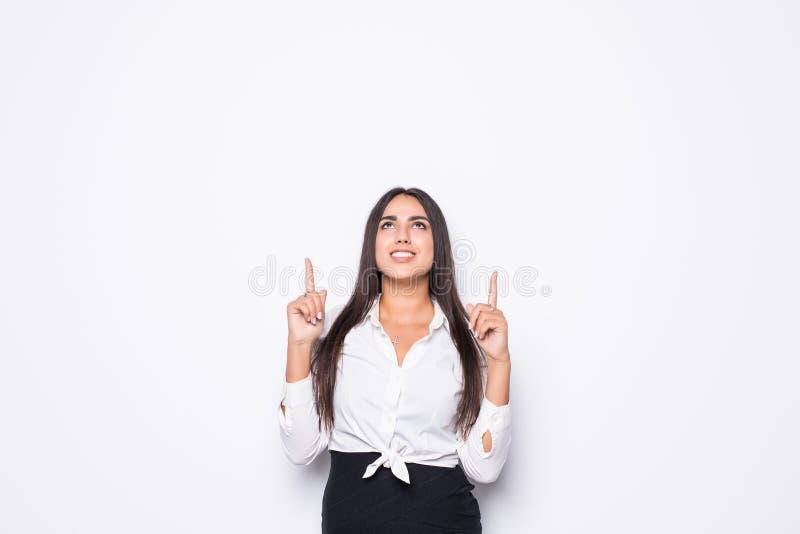 Ritratto di una donna di affari di buon umore vestita in vestito che indica sul dito via allo spazio della copia isolato sopra fo fotografia stock libera da diritti