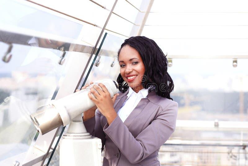Ritratto di una donna di affari felice che guarda con il paesaggio urbano del binocolo immagini stock
