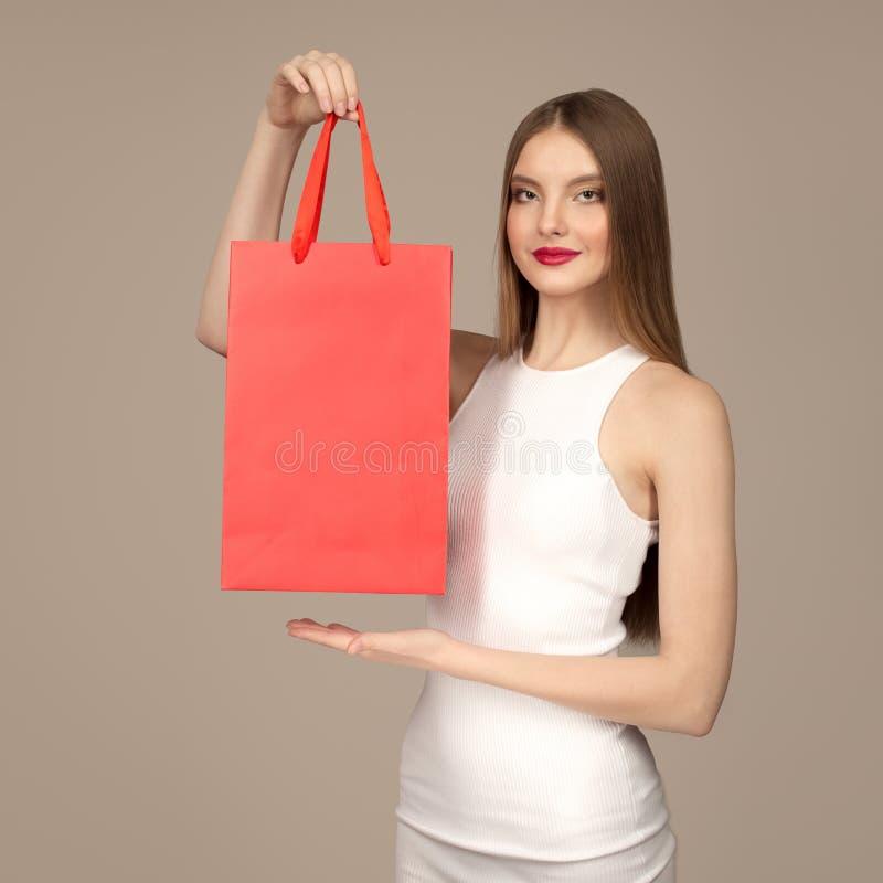 Ritratto di una donna affascinante felice che tiene i sacchetti della spesa rossi immagini stock libere da diritti