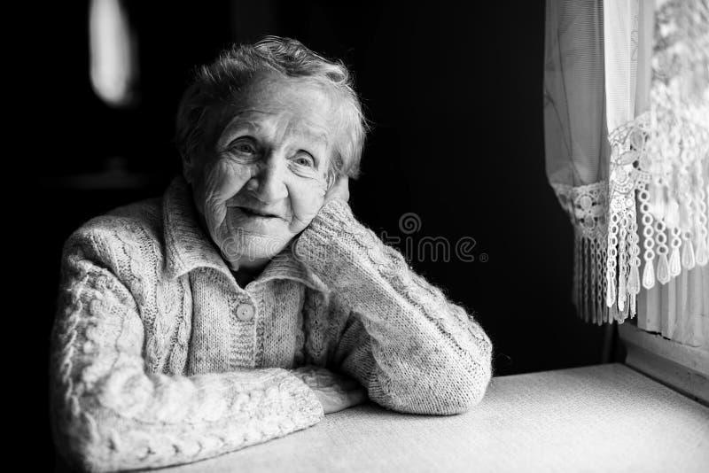 Ritratto di una donna anziana che si siede vicino alla finestra immagine stock