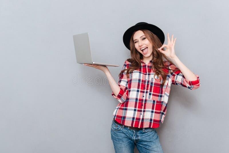 Ritratto di una donna attraente in pc della tenuta della camicia di plaid immagine stock libera da diritti