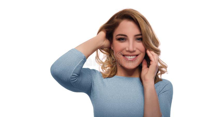 Ritratto di una donna attraente in un vestito blu su un fondo bianco immagine stock
