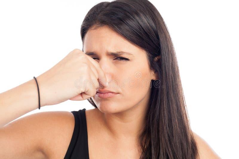 Ritratto di una donna brunetta che si pizzica il naso a causa di un cattivo odore immagini stock libere da diritti