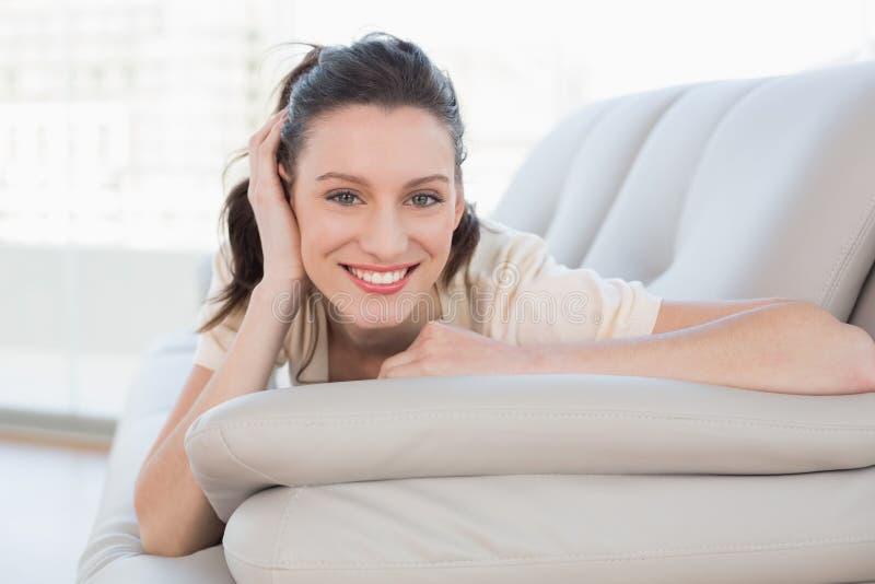 Ritratto di una donna casuale sorridente che si trova sul sofà immagini stock libere da diritti