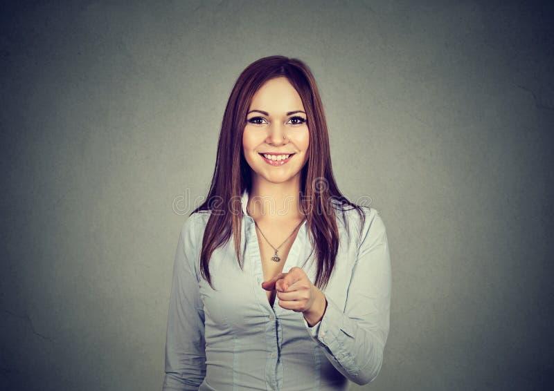 Ritratto di una donna che sorride e che indica alla macchina fotografica fotografia stock