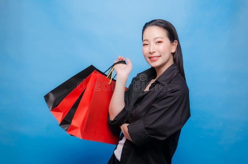 Ritratto di una donna cinese felice in camicia nera che giudica i sacchetti della spesa isolati su un fondo blu fotografia stock