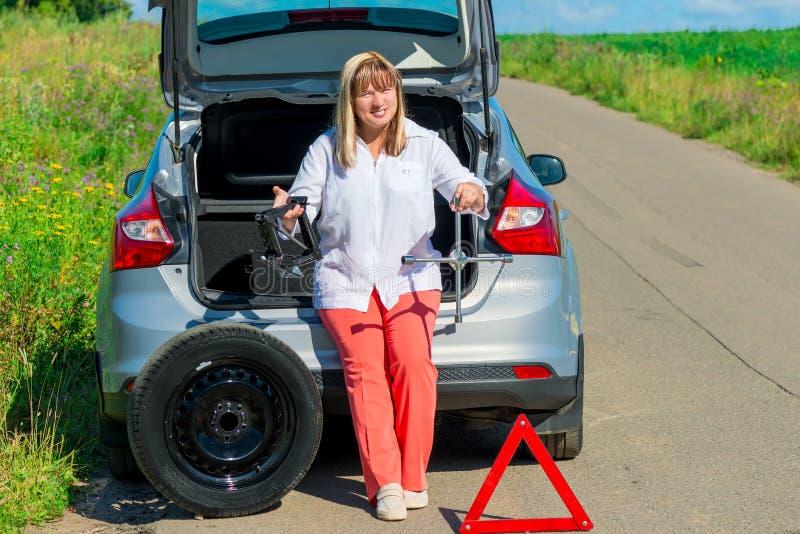 Ritratto di una donna con gli strumenti per il cambiamento della ruota fotografie stock libere da diritti