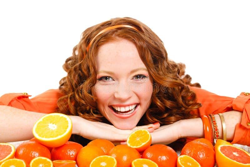 Ritratto di una donna con le arance su bianco fotografia stock
