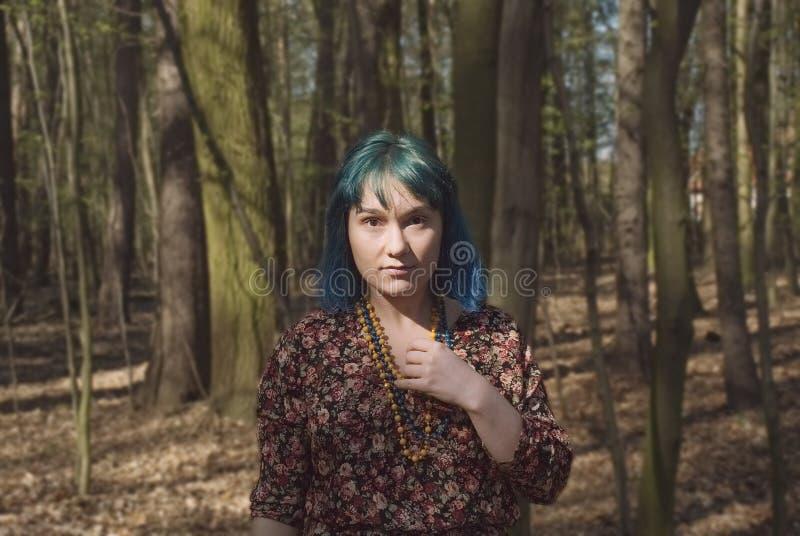 Ritratto di una donna con un aspetto interessante che cammina nel legno immagini stock