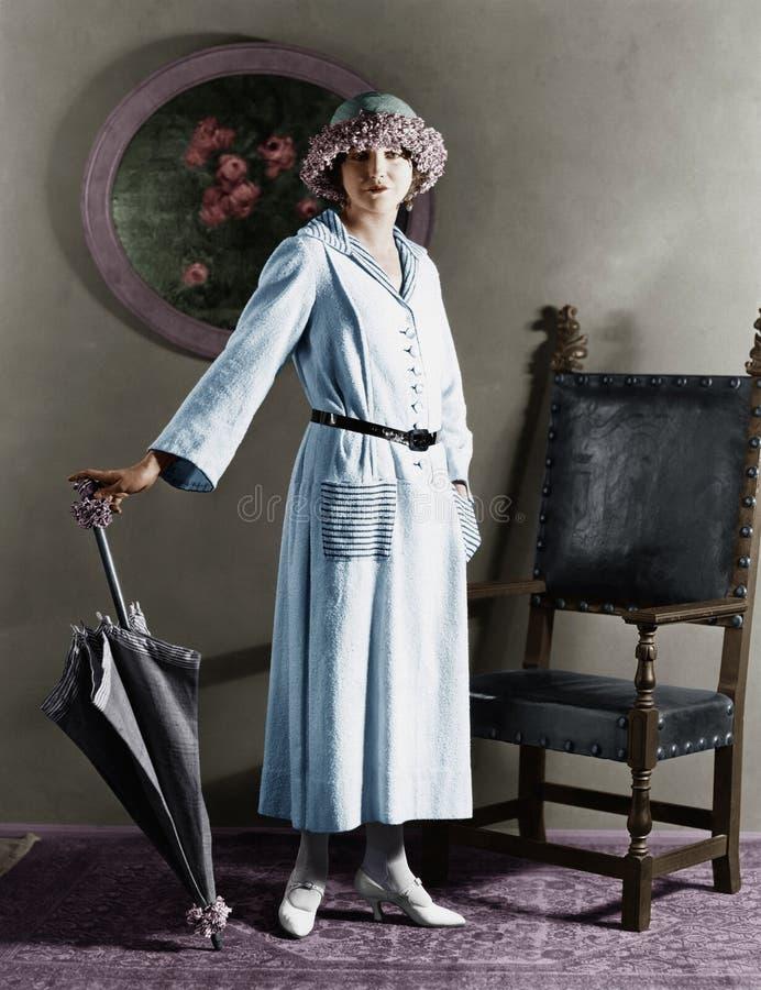 Ritratto di una donna con un cappello che sta con un ombrello (tutte le persone rappresentate non sono vivente più lungo e nessun immagini stock libere da diritti