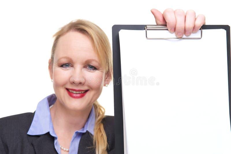 Ritratto di una donna di affari che mostra lavagna per appunti in bianco immagini stock