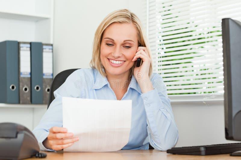 Ritratto di una donna di affari che telefona e che legge immagine stock