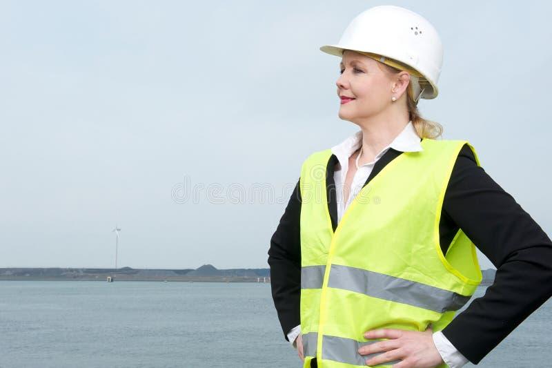 Ritratto di una donna di affari in elmetto protettivo che sta all'aperto fotografie stock libere da diritti