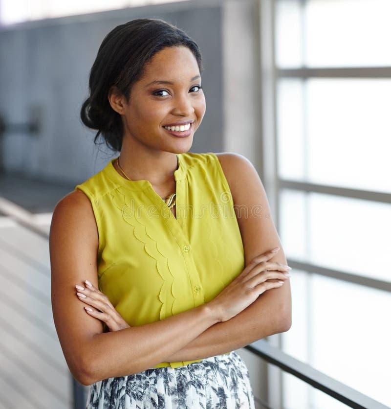 Ritratto di una donna di affari nera sicura sul lavoro nel suo ufficio di vetro fotografia stock