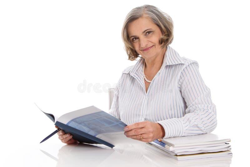 Ritratto di una donna di affari sorridente più anziana che si siede allo scrittorio fotografia stock libera da diritti