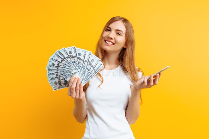 Ritratto di una donna emozionante che mostra le fatture di soldi e che giudica telefono cellulare isolato su fondo giallo immagine stock libera da diritti