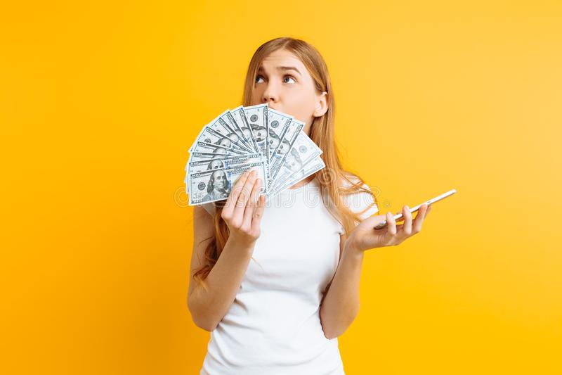 Ritratto di una donna emozionante che mostra le fatture di soldi e che giudica telefono cellulare isolato su fondo giallo fotografia stock libera da diritti
