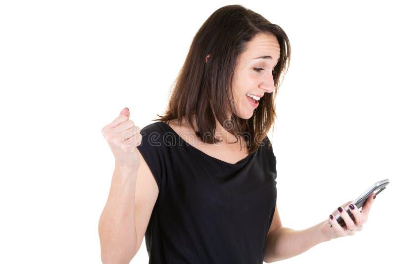 Ritratto di una donna emozionante nelle buone notizie leggenti nere in uno Smart Phone sul fondo bianco della parete immagini stock