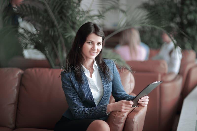 Ritratto di una donna esecutiva di affari con una lavagna per appunti sui precedenti del centro di affari immagini stock