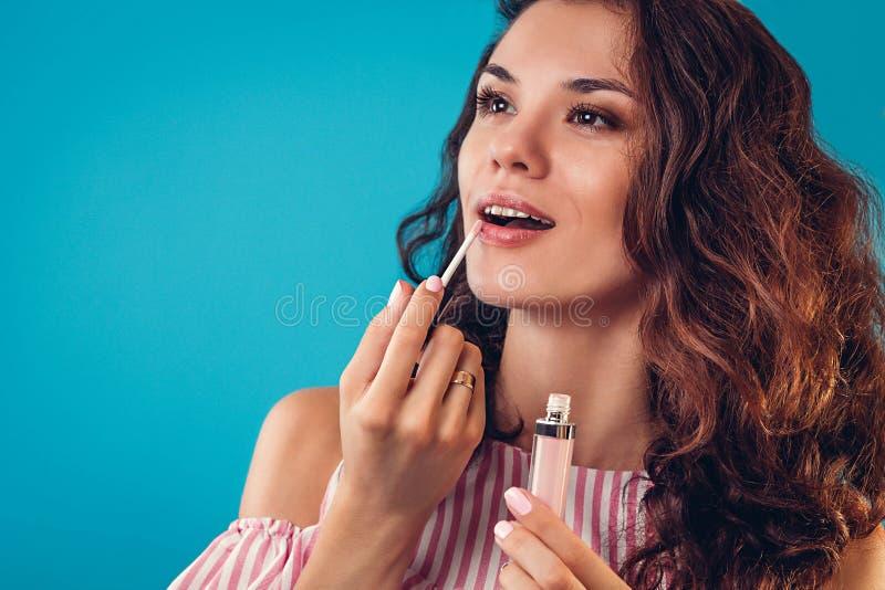 Ritratto di una donna graziosa che applica un rossetto immagini stock libere da diritti