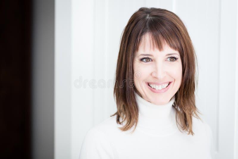 Ritratto di una donna graziosa che sorride, distogliendo lo sguardo, isolato su bianco fotografie stock