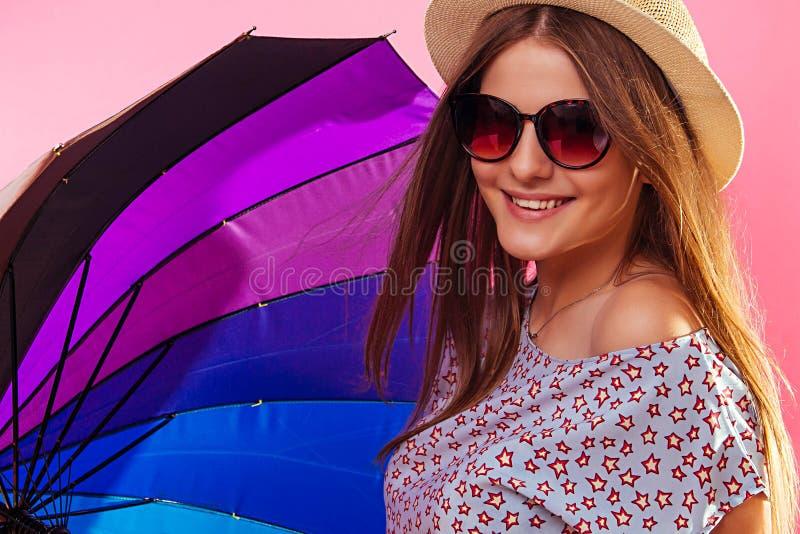 Ritratto di una donna graziosa con gli occhiali da sole d'uso dell'ombrello clororful fotografia stock libera da diritti