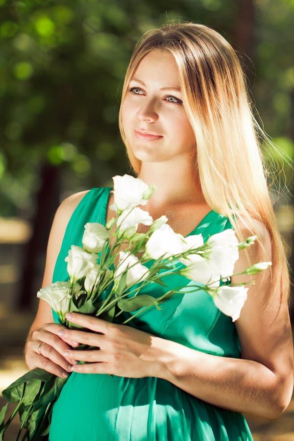 Ritratto di una donna incinta bionda con i fiori in loro mani fotografia stock