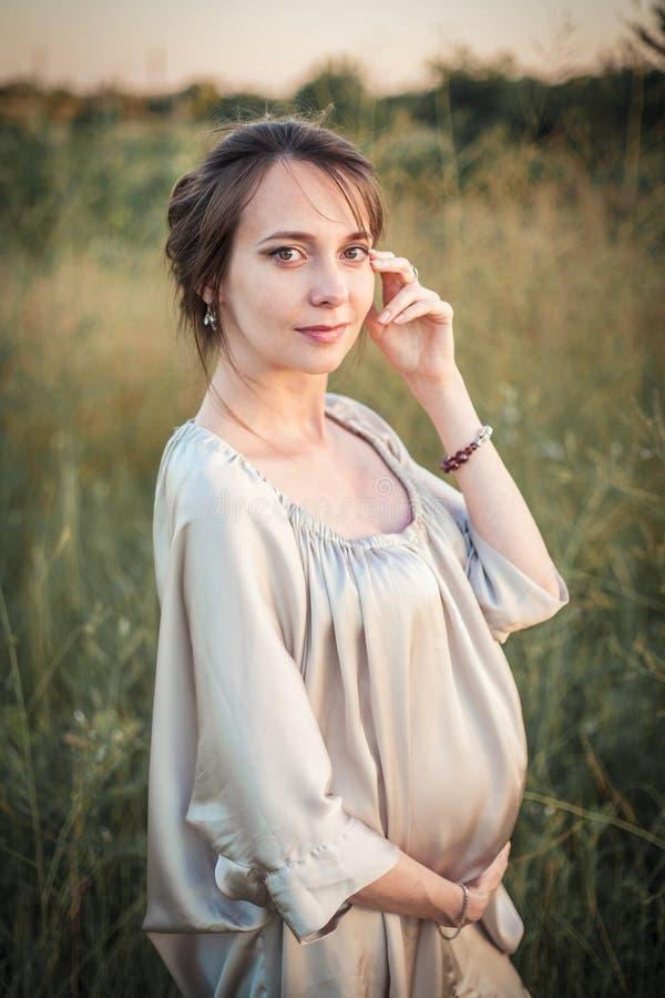 Ritratto di una donna incinta sulla natura fotografia stock libera da diritti
