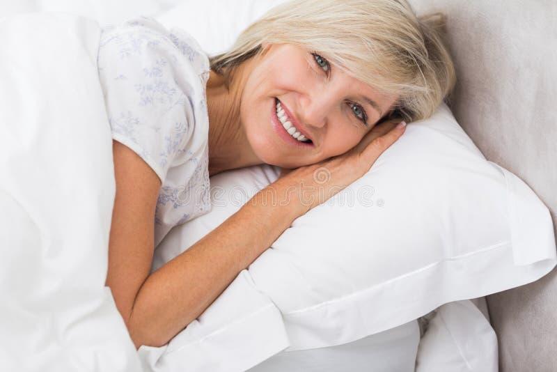 Ritratto di una donna matura che riposa a letto fotografia stock libera da diritti