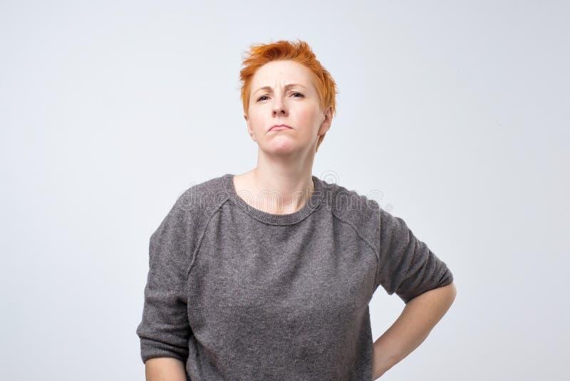 Ritratto di una donna di mezza età triste con brevi capelli rossi su un fondo grigio fotografia stock