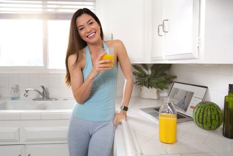 Ritratto di una donna mista castana calda ed amichevole, in buona salute, adatta, sorridente di etnia che gode di una bevanda del immagine stock