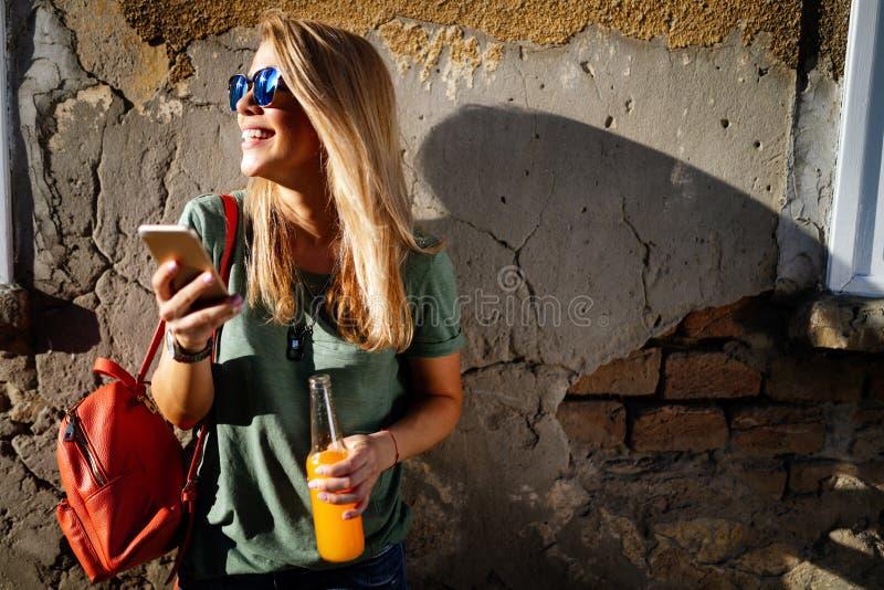 Ritratto di una donna molto sorridente che usa il cellulare mentre tiene in mano un drink immagine stock