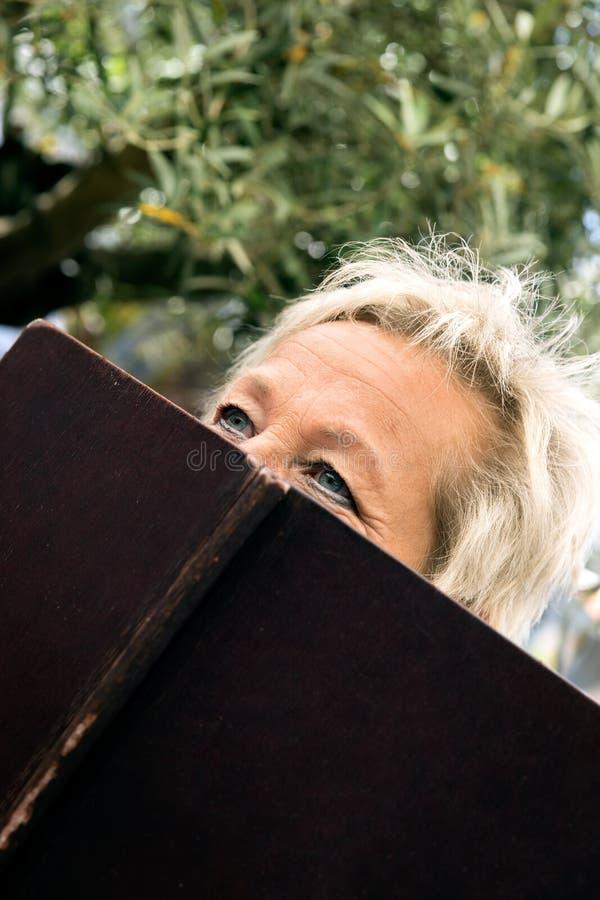 Ritratto di una donna più anziana attraente dietro un menu fotografie stock libere da diritti