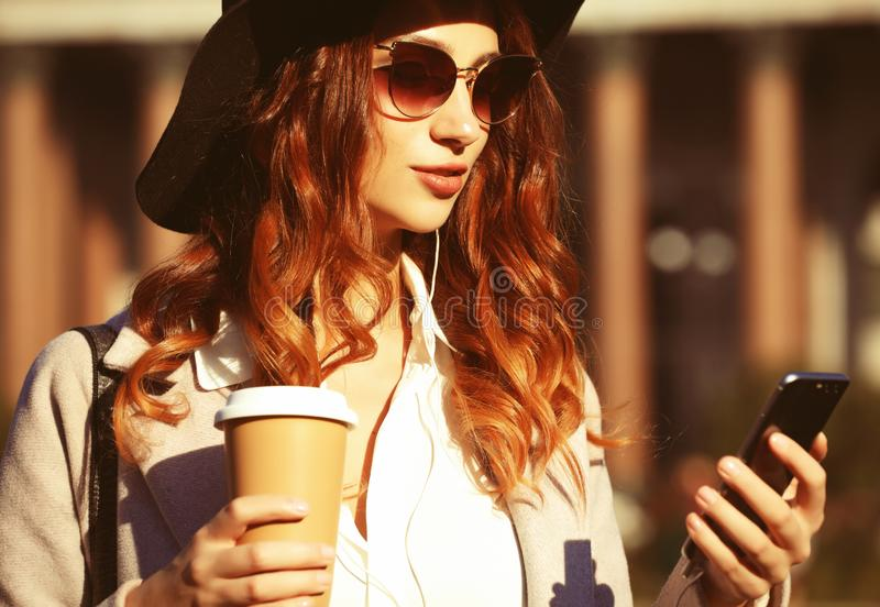 Ritratto di una donna piuttosto sorridente che usa il cellulare mentre tiene la tazza di caffè su una strada della città fotografia stock
