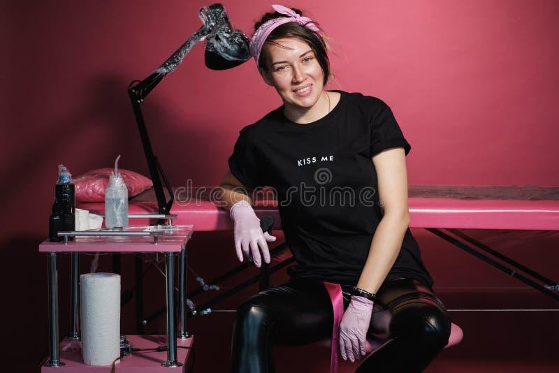 Ritratto di una donna professionale del padrone del tatuaggio Vestiti neri e dreadlocks Priorit? bassa rossa, dentellare e bianca fotografia stock