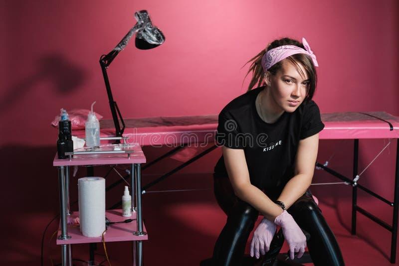 Ritratto di una donna professionale del padrone del tatuaggio Vestiti neri e dreadlocks Priorit? bassa rossa, dentellare e bianca immagine stock