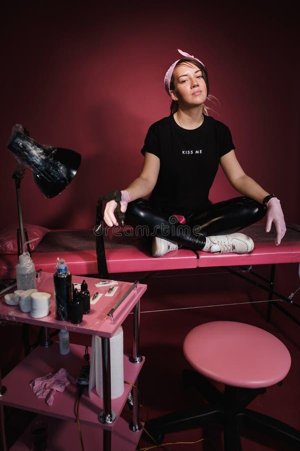 Ritratto di una donna professionale del padrone del tatuaggio Vestiti neri e dreadlocks Priorit? bassa rossa, dentellare e bianca fotografia stock libera da diritti