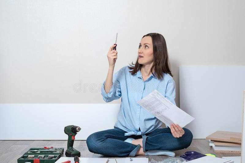 Ritratto di una donna sorpresa e imbarazzata sul pavimento con un cacciavite e delle istruzioni per il montaggio di mobilia fotografia stock libera da diritti