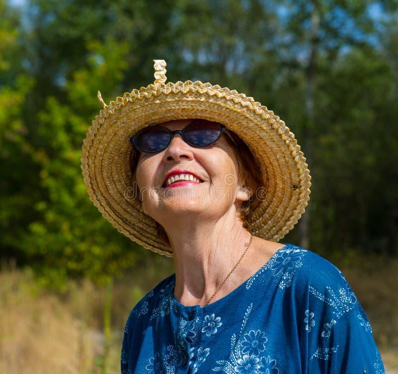 Ritratto di una donna sorridente in cappello di paglia ed occhiali da sole fotografia stock libera da diritti