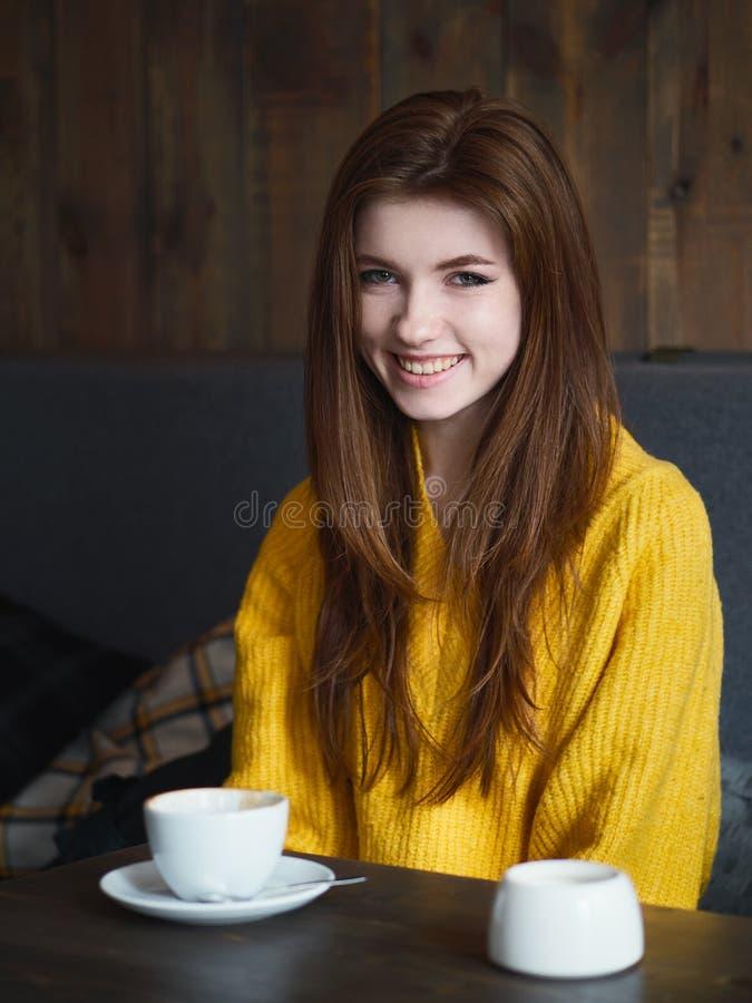 Ritratto di una donna sorridente della testarossa graziosa sveglia che si siede in un caffè che gode della pausa caffè di tempo immagine stock libera da diritti