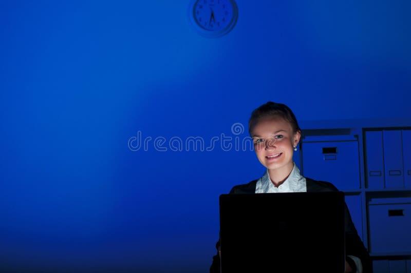 Ritratto di una donna in un ufficio di notte immagini stock libere da diritti