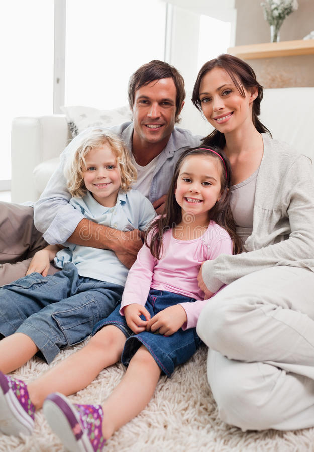 Ritratto di una famiglia che si rilassa nel loro salone immagini stock