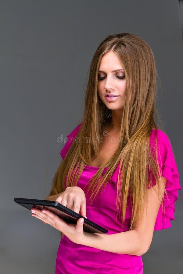 Ritratto di una giovane donna alla moda attraente con il PC della compressa fotografia stock libera da diritti