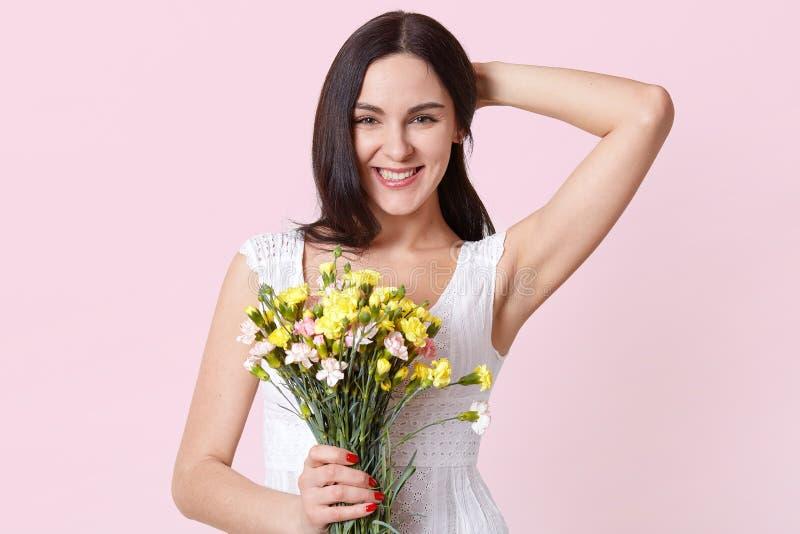Ritratto di una giovane donna allegra felice in vestito bianco da estate che tiene i fiori colourful in una mano, riparando i suo fotografia stock