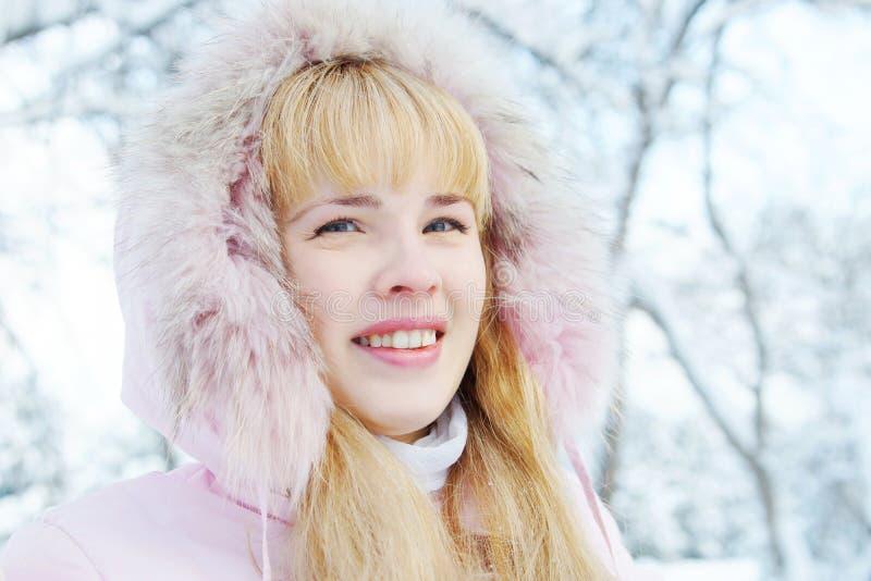 Ritratto di una giovane donna bionda sveglia che porta un rivestimento rosa con un cappuccio immagine stock libera da diritti
