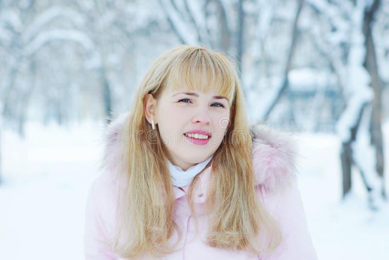 Ritratto di una giovane donna bionda sveglia dai capelli lunghi all'aperto nell'inverno fotografia stock