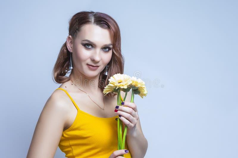Ritratto di una giovane donna caucasica tranquil posata in abiti gialli con fiori Bouquet fotografia stock libera da diritti