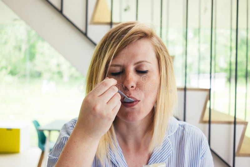Ritratto di una giovane donna che assaggia alimento fotografia stock
