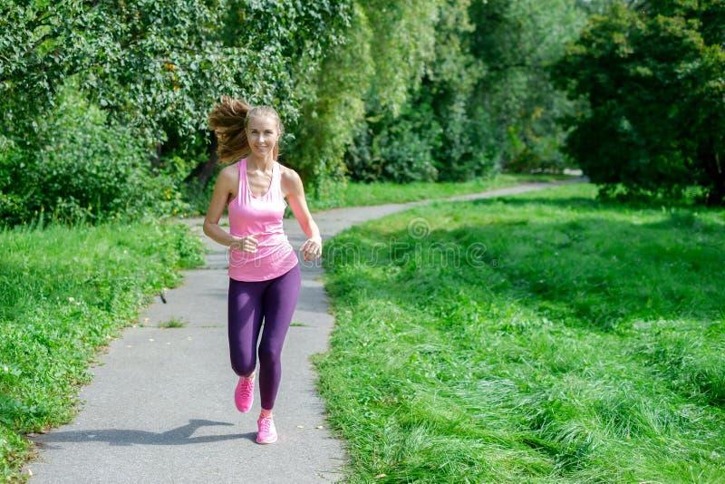 Ritratto di una giovane donna che corre da solo nel parco immagine stock libera da diritti