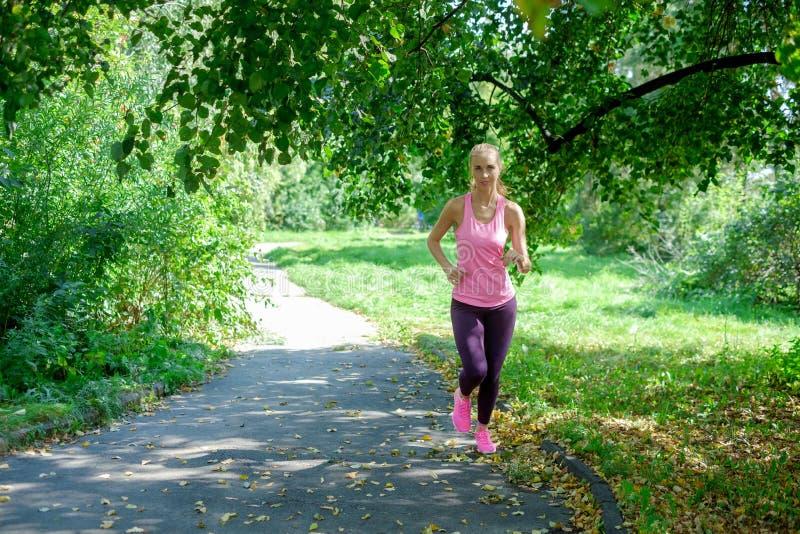 Ritratto di una giovane donna che corre da solo nel parco fotografia stock libera da diritti
